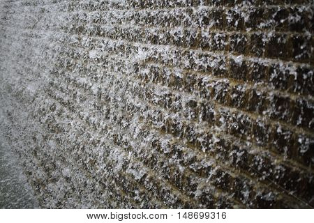 Dark brick wall with a stream of water from a fountain