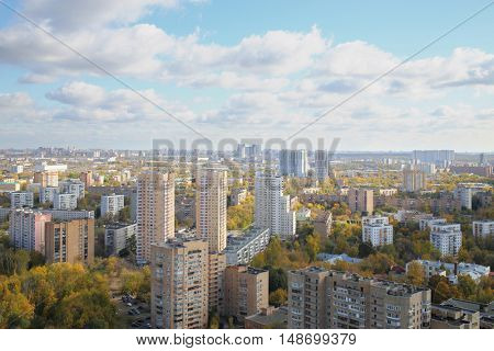 Panorama of the city with high-rise buildings and blue sky with clouds in autumn
