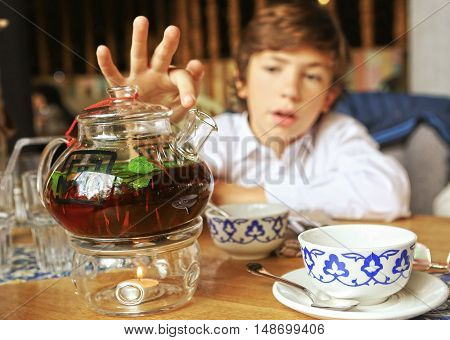 tea pot with welding and mint leafs cup on the table preteen boy on the background