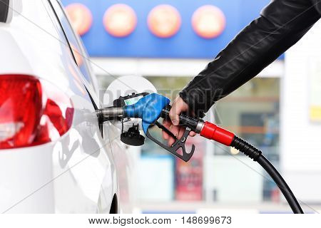 Hand refilling the car with fuel. Refueling