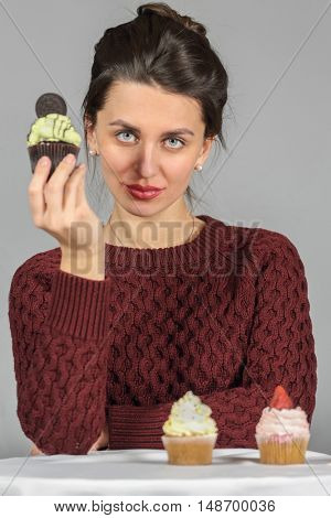 Half-length portrait of woman in burgundy sweater holding piece of tasty chocolate cake, on gray background