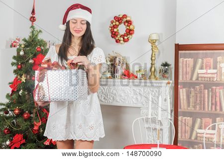 young pretty woman near new year tree with christmas present and rose