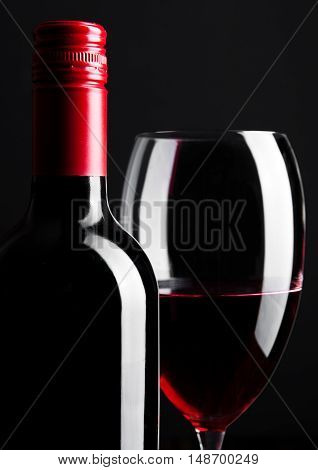 Red wine bottle and glass closeup on black background