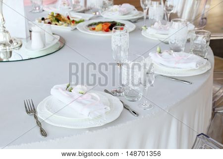restaurant table with empty glasses and a plate with a napkin close up
