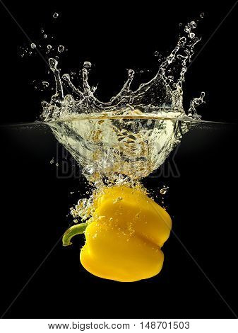 Yellow bell pepper falling in water with splash on black background.