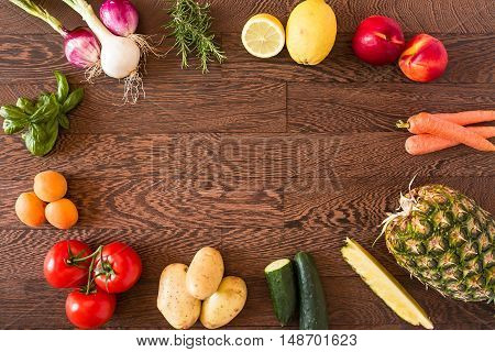 Assorted raw vegetables and fruits over a wooden background