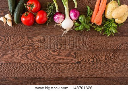 Assorted raw vegetables over a wooden background