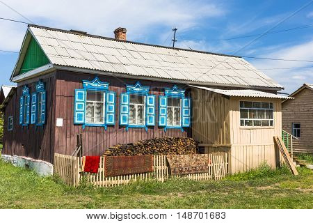 Picturesque village house with pile of firewood behind the wooden fence.