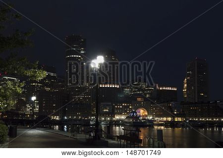 Street lights illuminate Harborwalk along Fan Pier with Rowes Wharf in background