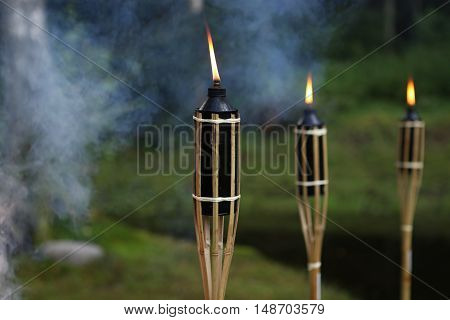 Three bamboo torches burn in smoky nature