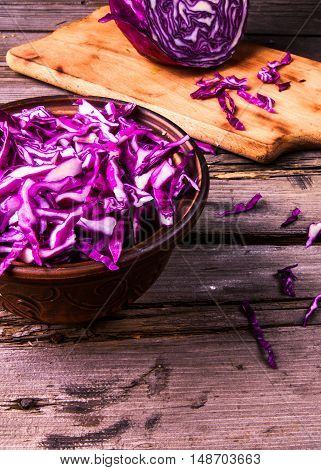 Sliced purple cabbage in a bowl, and the residue of it on a cutting board. Vitamin autumn meal. Copy space, on wooden table
