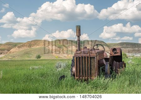 very old rusted tractor sitting in a green field with hills in the background under a bright blue sky in the summer time