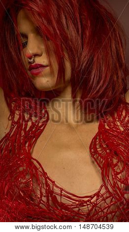 beautiful redhead with pierced nose and red corset lace frills wax
