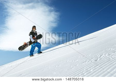 Snowboarder goes hill on the blue sky backdrop in mountains. Sheregesh, Siberia, Russia