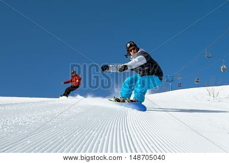 Bright color snowboarders ride on blue sky backdrop. Sheregesh, Siberia, Russia