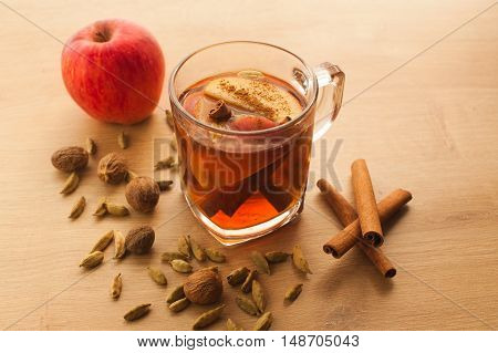 Hot tea with apple, cinnamon and cardamom. Autumn healthy drink to warm yourself in cold weather. Vitamin beverage with spices.