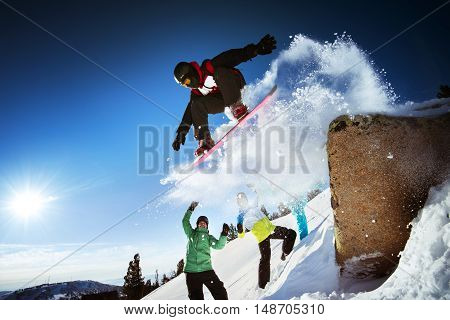 Bright color snowboarder jumps on blue sky backdrop. Sheregesh, Siberia, Russia