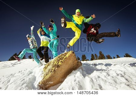 Bright color snowboarders jump of big stone on blue sky backdrop. Sheregesh, Siberia, Russia