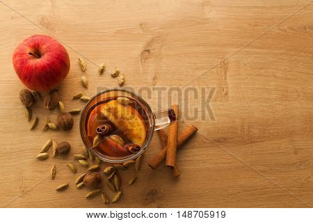 Closeup with free space of hot tea with apple, cinnamon and cardamom. Autumn healthy drink to warm yourself in cold weather. Vitamin beverage with spices.