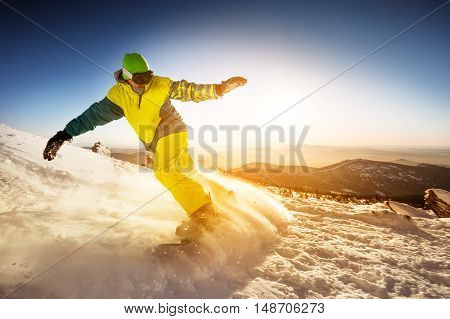 Snowboarder rides on the slope on snow mountains background. Sheregesh resort, Siberia, Russia