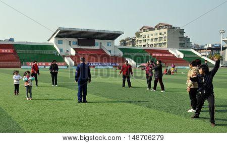 Pengzhou China - December 11 2013: Chinese men women and children performing Tai 'chi exercises in Pengzhou National Stadium