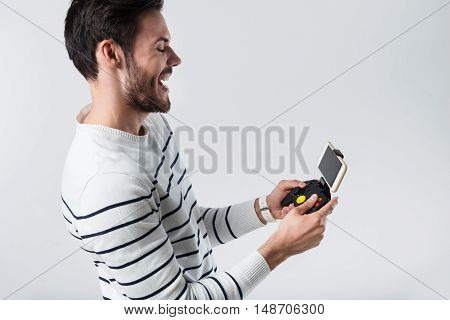 Crazy mood. Young emotional man shouting and using portable gamepad while standing against white background.