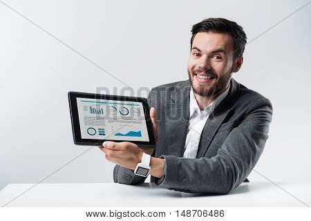 Grate results. Young handsome man smiling and showing diagrams on tablet while sitting against white background.