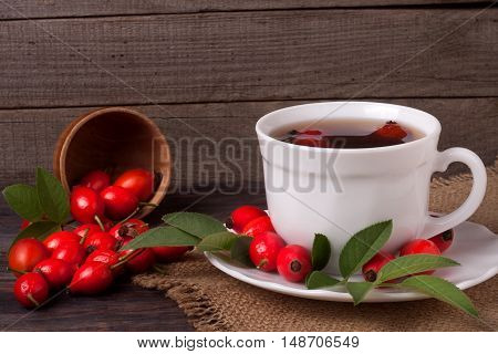 Tea from the hips on the wooden background.