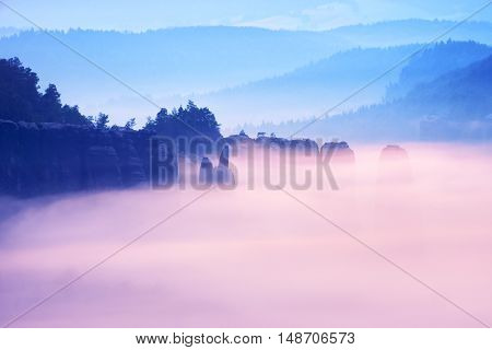 Misty Melancholy Daybreak In Beautiful Fairy Valley. Peaks Of Rock Trim Creamy Foggy Clouds