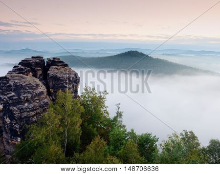 Sharp Sandstone Cliffs Above Deep Misty Valley. Popular Climbers Resor