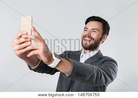 Let me take a selfie. Young handsome glad man smiling and using smartphone while standing against white background.