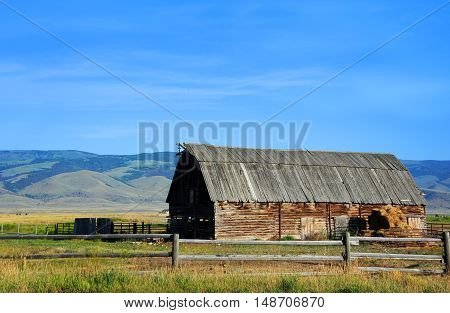Log barn with wooden roof sits in Happy Valley Montana. Mountains and blue sky form background.