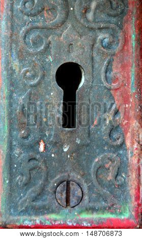 Background image shows key hole in antique metal plate. Door was painted red.