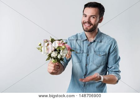 Be my Valentine. Young amorous handsome man holding a bunch of flowers and smiling while standing against white background.