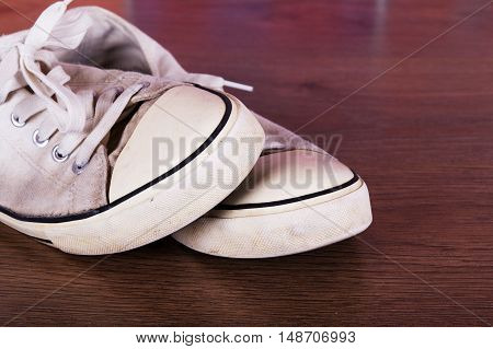 Old Canvas Shoes On A Wooden Floor