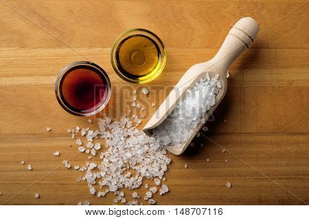 coarse salt oil and vinegar on a wooden board