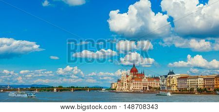 Panorama with building of Hungarian parliament at Danube river in Budapest city. Hungary. Blue sky clouds