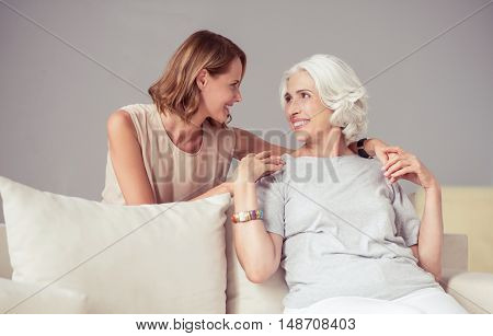 Best friends. Positive delighted aged woman sitting on the sofa and looking at her adult beautiful daughter while resting at home together