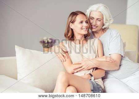 Connection of generations. Joyful aged smiling woman sitting on the couch with her beautiful adult daughter and embracing while relaxing