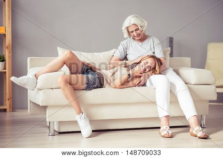 Childish mood. Joyful delighted smiling woman lying on the couch and expressing joy while resting at home with her mother