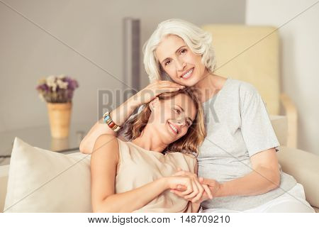 Full of emotions. Cheerful smiling senior woman and her daughter sitting on the couch and expressing joy while embracing