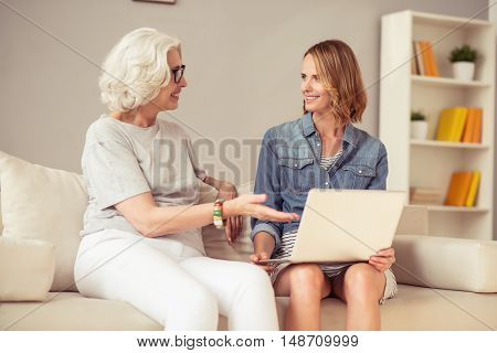 Involved in process. Cheerful delighted woman smiling and sitting on the sofa with her adult beautiful daughter while using laptop
