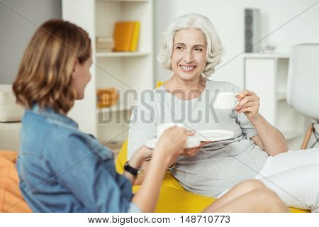 Relief stress. Positive delighted smiling adult woman talking with her adult daughter and drinking coffee while resting at home