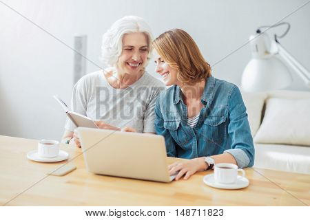 Happy to spend time together. Positive delighted mother and her adult beautiful daughter sitting at the table and looking in the book while resting together