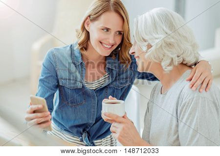 Close relations. Cheerful content smiling woman holding cell phone and embracing her aged mother while resting together