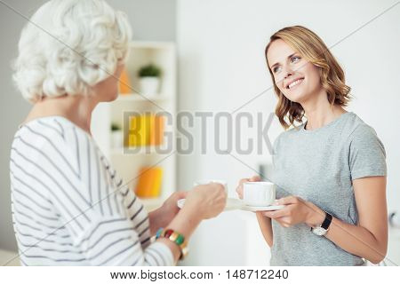 Enjoy every day. Positive content beautiful woman holding cup and drinking coffee while talking with her aged mother