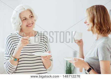 Glad together. Joyful content woman and her adult daughter drinking coffee and having a pleasant conversation while resting together