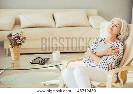 time for dreams. Pleasant delighted aged woman closing her eyes and sitting in the chair while holding big book in hands