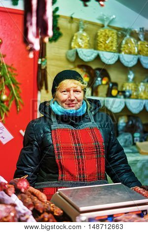 Riga Latvia - December 24 2015: Smiling woman selling traditional latvian goods at the Riga Christmas Market. At the market people can find various souvenirs warm clothes food and drinks.
