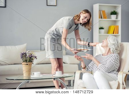 Try it. Positive delighted beautiful woman holding plate with pie and giving it to her aged mother